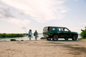 Two people alongside a lake with their Rivian R1S SUV