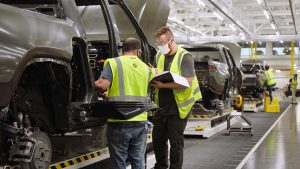 Two men working in an auto factory