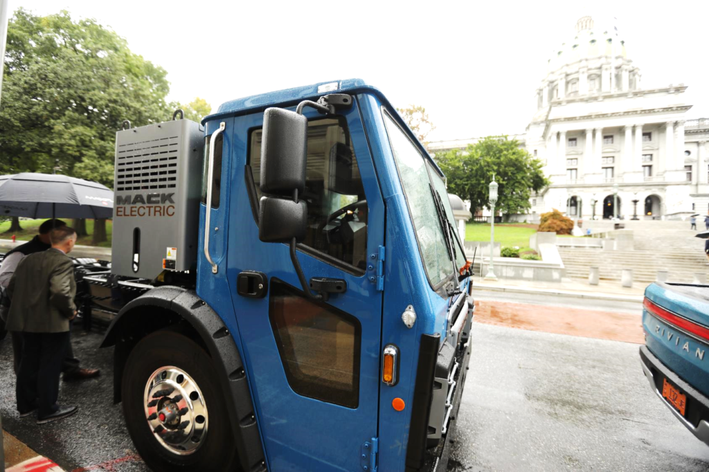 A Mack electric refuse truck in front of the Pennsylvania capitol building